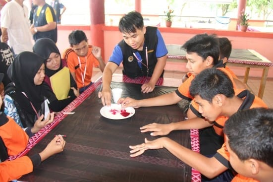 One UTM students (black vest) facilitate participants doing the group activities at SciMEx 2014 at Bandar Tenggara