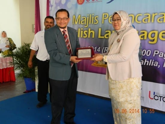 Assoc. Prof. Dr. Nur Naha (right) handing souvenirs to Hermee Tahir on the launching ceremony of UTM English Enrichment Program at SK Taman Bukit Dahlia, Pasir Gudang.