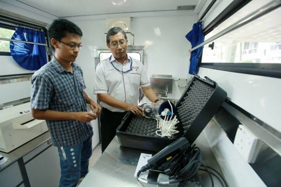 Prof. Razman (right) and one of his post-graduates students showing one of the water analysis tools available on board of UTM Mobile Laboratory.