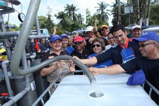 From left, Dr Ewon Ebin, Prof. Wahid Omar and Dr. Sheikh Muszaphar (holding the pipe) at the launching ceremony of UTM Portable Water Filter Machine at Pekan, Pahang.
