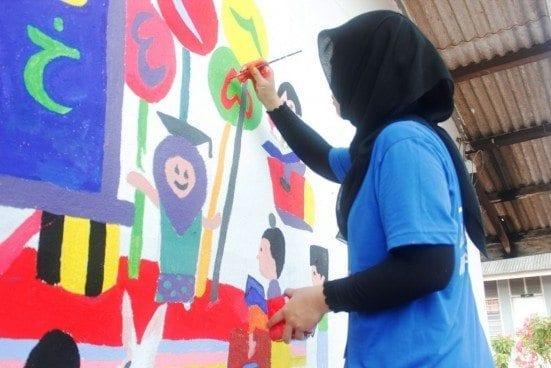 The UTM JETS 2015 participants assisting the Sekolah Agama Felda Sening pupils in painting the school building.