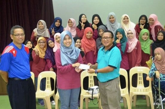 Nurfatiha Ramli (second left) handing over the donation to the representative from Cerebral Palsy Society.
