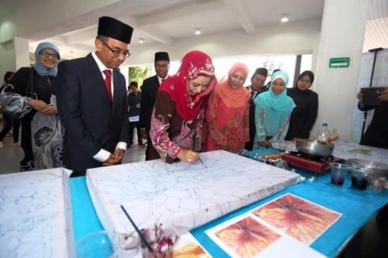 HRH Raja Zarith Sofia (third left) was trying the canting batik at the Batik Canting exhibition held at UTM Faculty of Built Environment. Accompanying Raja Zarith was UTM Vice Chancellor, Prof. Datuk Ir. Dr. Wahid Omar (second left).