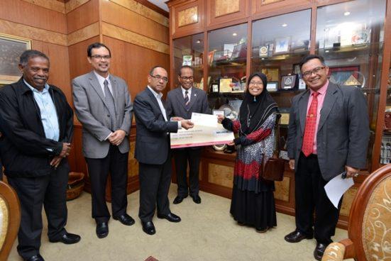 Datuk Wahid menyampaikan cek kepada Juhaida sambil disaksikan oleh Wan Mohd Zawawi (tengah), Timbalan Pendaftar Kanan Hasan Husin (kiri) Azlan (dua dari kiri) dan Timbalan Pendaftar Kanan Dahari Derahi (kanan).