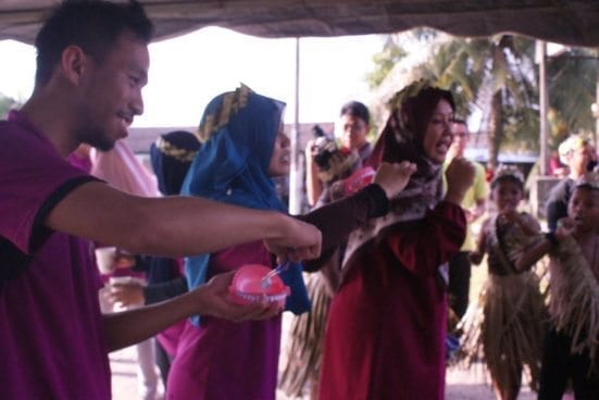 Showing the most effective way in brushing teeth to Orang Asli community at Perling Orang Ali settlement.