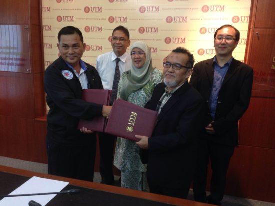 prof Zaimi dan Lim bertukar dokumen erjanjian.
