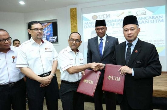 Prof. Wahid (third left) and Mohd Rofiki exchanging the MoA of establishing the UTM Education waqf at the Banquet Hall.